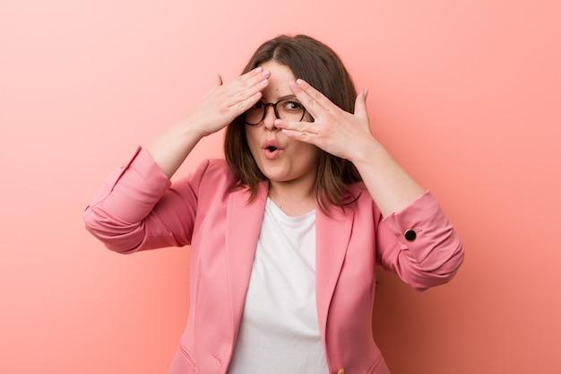 若いプラスサイズのビジネス白人女性は、恐怖と緊張の指の間で点滅します。