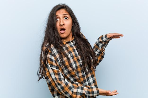 若いクールなインドの女性はショックを受け、手の間でコピーを保持して驚いた。