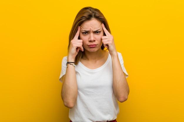 自然な白人の若い女性は、人差し指を頭に向けたまま、仕事に集中しました。