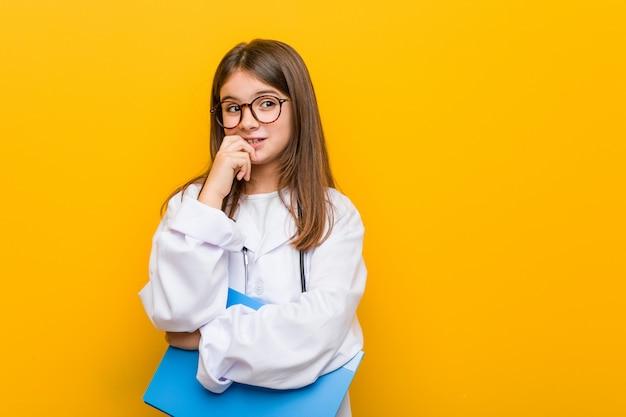 Маленькая кавказская девушка нося костюм доктора ослабила думать о что-то смотря экземпляр.