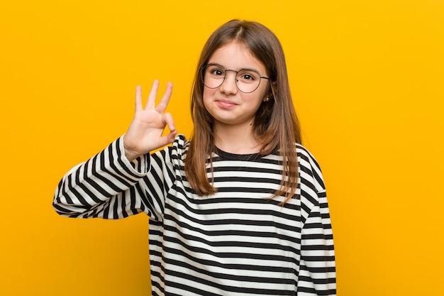 Маленькая кавказская милая девушка жизнерадостная и уверенно показывая одобренный жест.