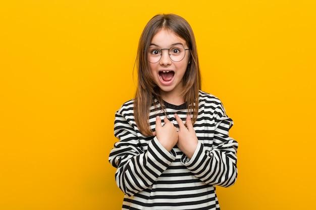 Маленькая кавказская милая девушка удивленно указывает на себя, широко улыбаясь.