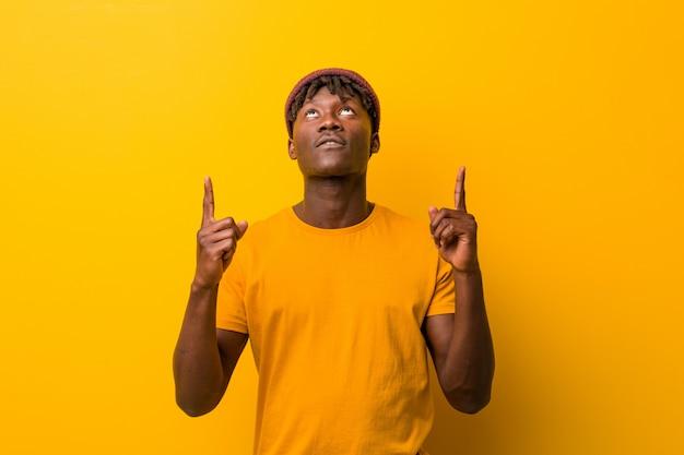 口を開けて逆さまに指している黄色の背景にラスタスを着ている若い黒人男性。