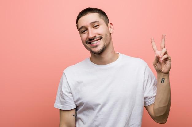 指で平和のシンボルを示すうれしそうな屈託のない若いカジュアルな男。
