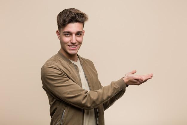 手のひらにコピーを保持している茶色のジャケットを着ている若い白人男。