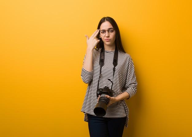 自殺ジェスチャーを行う若い写真家女性