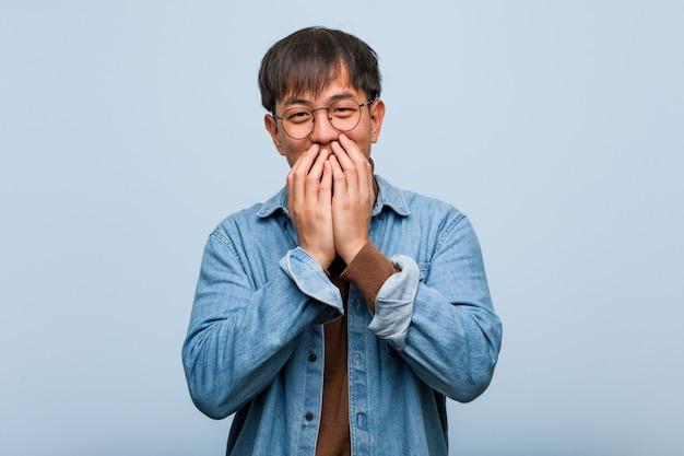 何かについて笑って、手で口を覆っている若い中国人男性