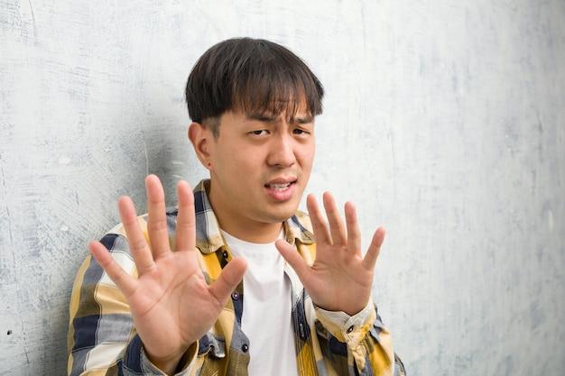 ジェスチャー嫌悪をしている何かを拒否する若い中国人の顔のクローズアップ