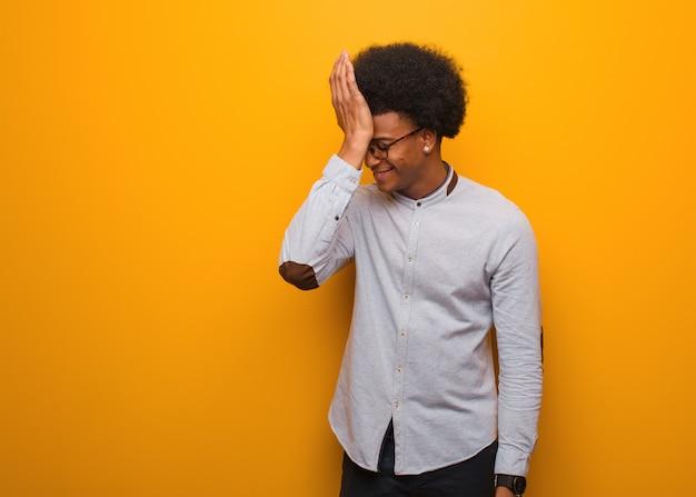 オレンジ色の壁を忘れて若いアフリカ系アメリカ人の男は、何かを実現します