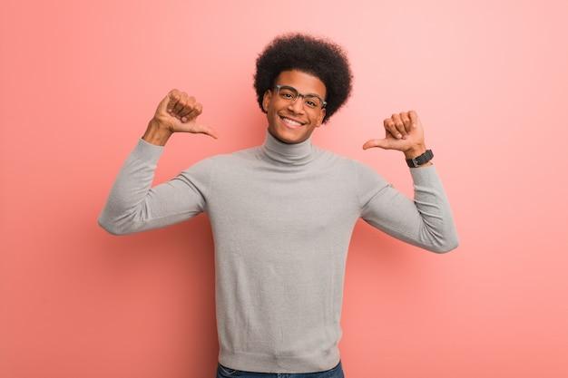 指を指すピンクの壁の上の若いアフリカ系アメリカ人男性、従う例