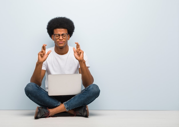 幸運のために指を交差ラップトップで床に座っている若い黒人男性