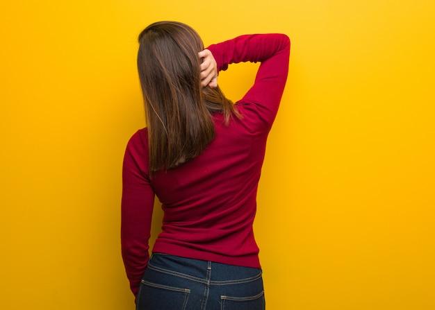 何かについて考える後ろから若い知的女性