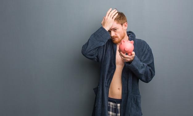 パジャマを着ている若い頭の男は心配し、圧倒されました。彼は貯金箱を持っています。