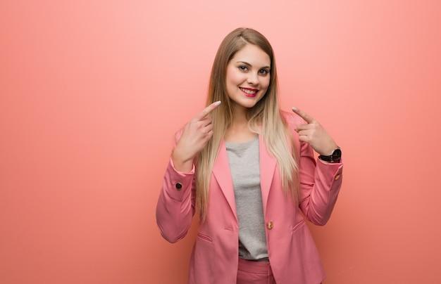 口を指しているパジャマ笑顔を着ている若いロシア人女性