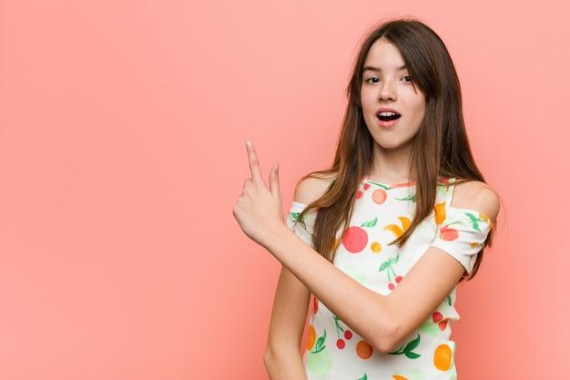 Девушка в летней одежде на фоне красной стены, указывая в сторону