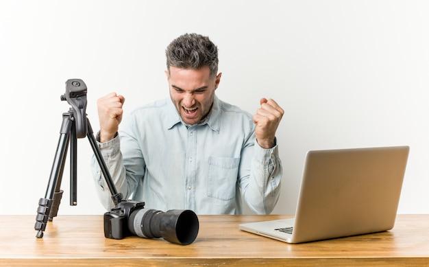 屈託のない、興奮して応援若いハンサムな写真の先生。勝利のコンセプト。