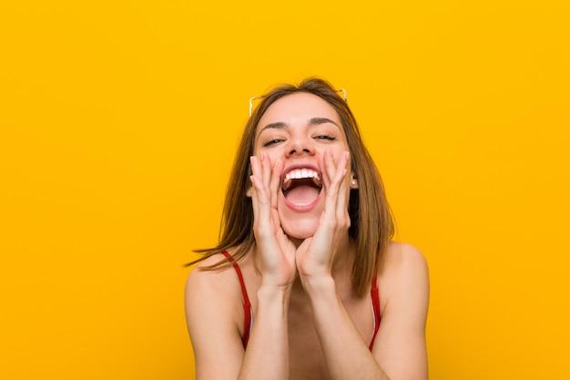 ビキニとサングラスを叫んで身に着けている若い白人女性は前に興奮しています。