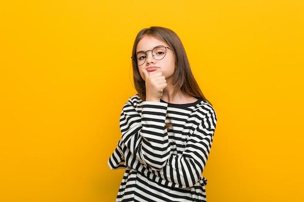 Маленькая кавказская милая девушка смотря косой с сомнительным и скептическим выражением.