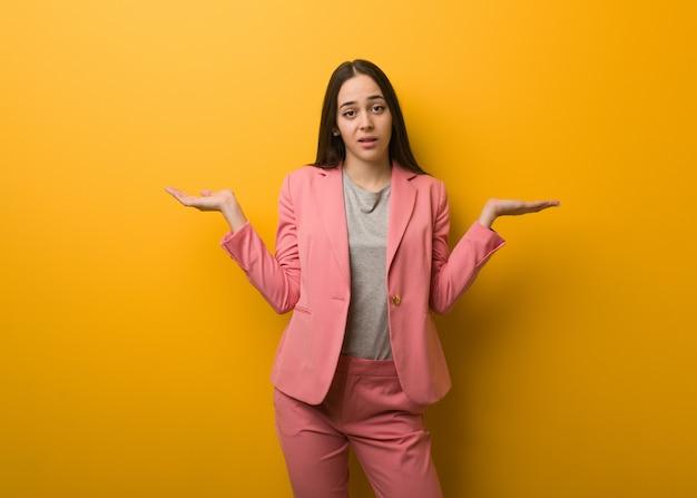 Молодая современная деловая женщина сомневаясь и пожимая плечами