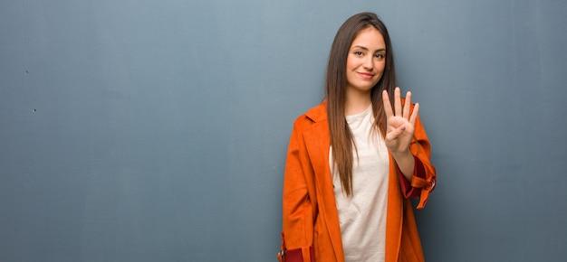 Молодая натуральная женщина показывает номер четыре