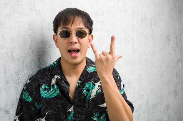 ロックジェスチャーを行う夏の服を着ている若い中国人男性