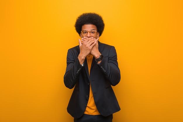 オレンジ色の壁を越えて驚いてショックを受けた青年実業家