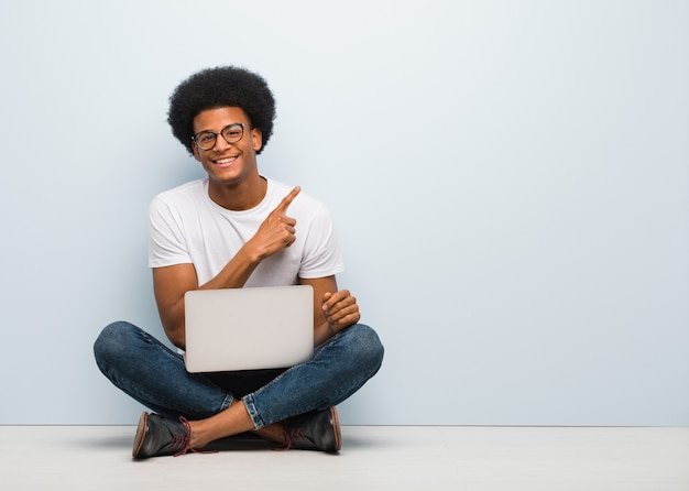 Молодой черный человек сидит на полу с ноутбуком, улыбаясь и указывая в сторону