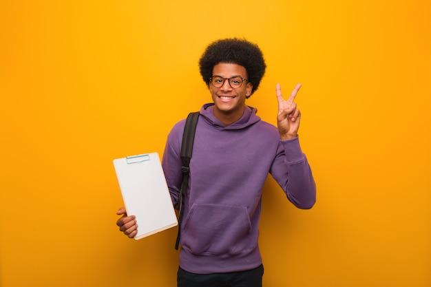 クリップボードの楽しさと幸せの勝利のジェスチャーをしている若い黒人学生男
