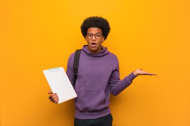 手のひらに何かを保持しているクリップボードを保持している若い黒人学生男