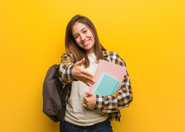 Молодой студент женщина протягивает руку, чтобы приветствовать кого-то