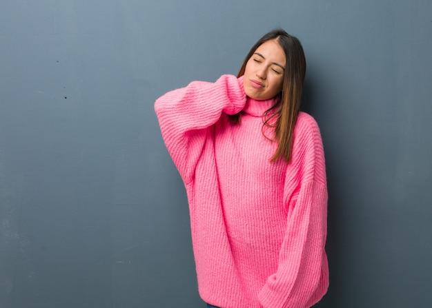首の痛みに苦しんでいる若い現代女性