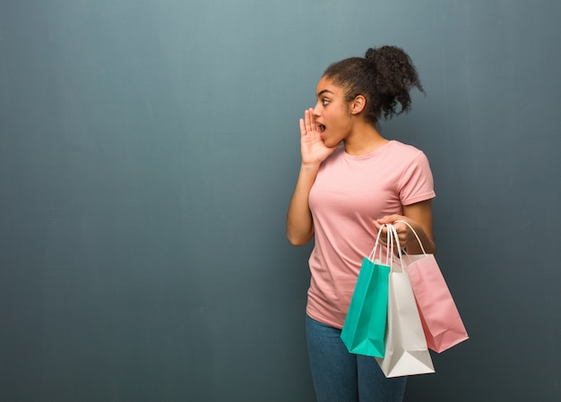 Молодая негритянка шепчет сплетни подтекст. она держит сумки для покупок.