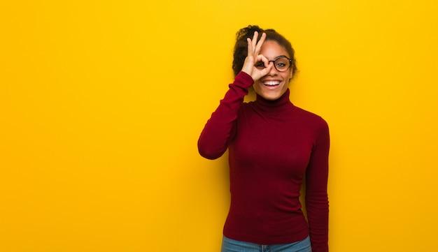 Молодая черная афроамериканская девушка с голубыми глазами уверенно делает хорошо жест на глаз