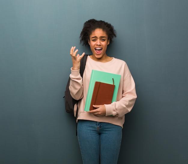 若い学生の黒人女性は非常に怖いと恐れています。彼女は本を持っています。