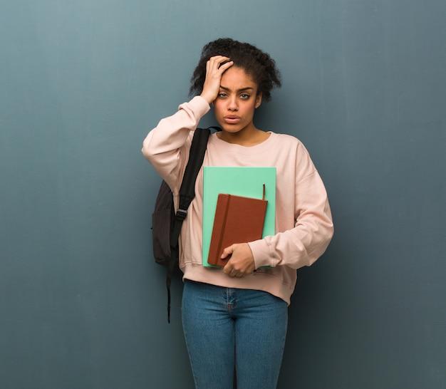 若い学生の黒人女性は疲れて非常に眠い。彼女は本を持っています。