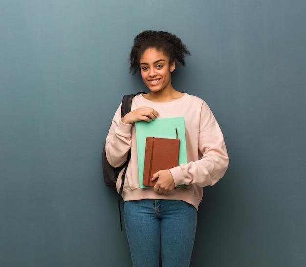 若い学生黒人女性の腕を交差、笑みを浮かべて、リラックスしました。彼女は本を持っています。