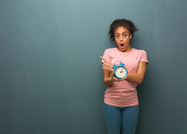 側を指している若い黒人女性。彼女は目覚まし時計を持っています。