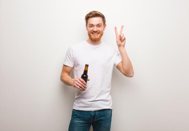 若い赤毛の男の楽しさと幸せの勝利のジェスチャーをしています。ビールを保持しています。