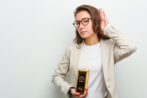 ゴシップを聴こうとして金塊を保持している若いヨーロッパの女性。