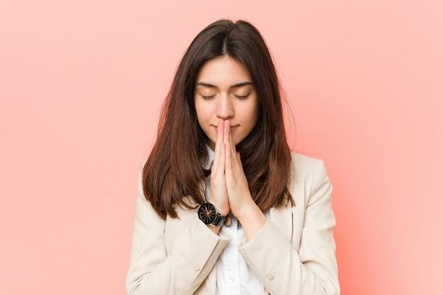 口の近くで祈って手を繋いでいる若いブルネットの女性は自信を持っています。