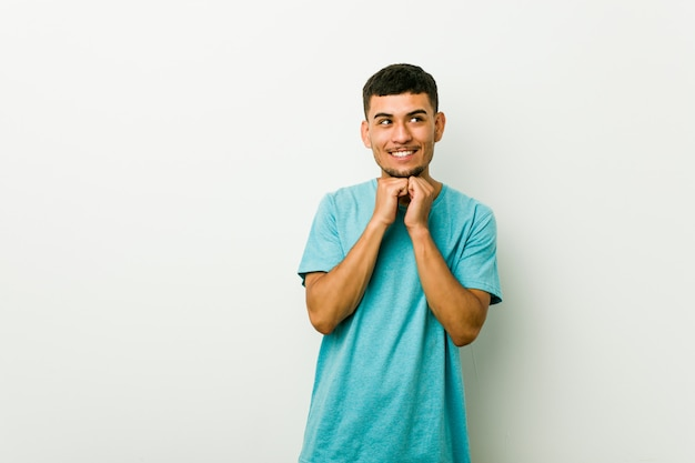 Молодой латиноамериканский человек держит руки под подбородком, счастливо смотрит в сторону.