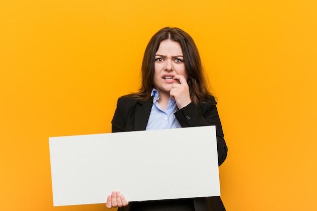 爪をかむ空白のプラカードを保持している若いプラスサイズの曲線の女性、神経質で非常に不安。
