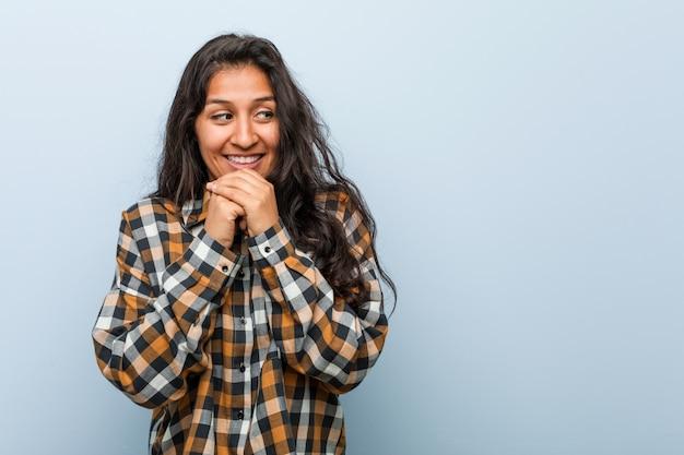 Молодая спокойная индийская женщина держит руки под подбородком, счастливо смотрит в сторону.