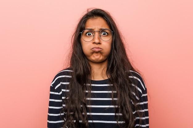 Молодая интеллигентная индийская женщина дует в щеки, устало выражение лица. концепция выражения лица.