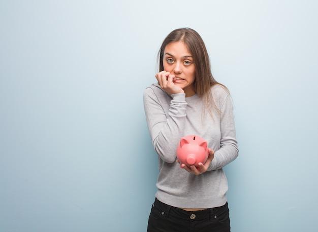 爪をかむ若いかなり白人女性、神経質で非常に心配しています。彼女は貯金箱を持っています。