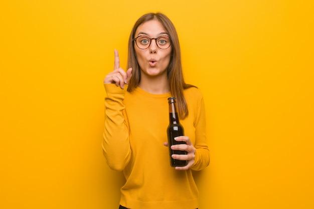 Молодая милая кавказская женщина имея отличную идею, концепцию творческих способностей. она держит пиво.
