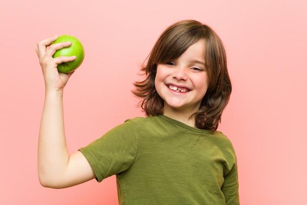 Маленький кавказский мальчик держа яблоко