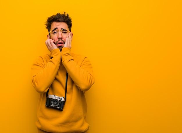 若い写真家の男は絶望的で悲しい