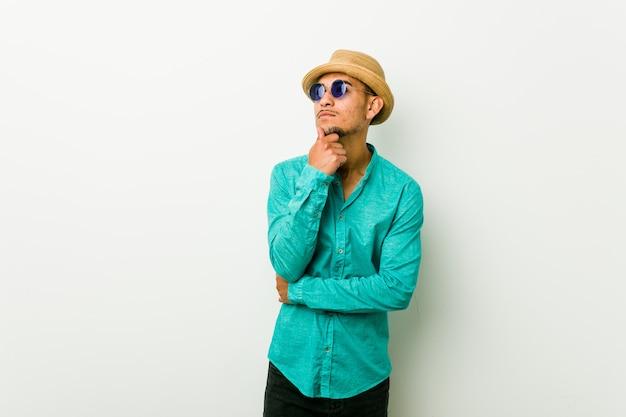 Молодой человек испаноязычное ношение летней одежды, глядя в сторону с сомнительным и скептическим выражением.