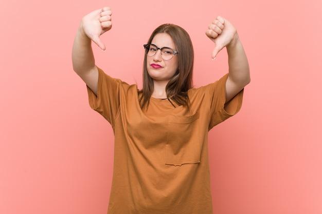 親指を下に示し、嫌悪感を表現する眼鏡を着ている若い学生女性。